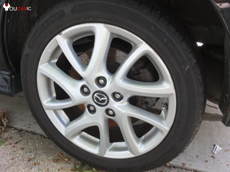 remove wheel to change brake pads on Mazda 5